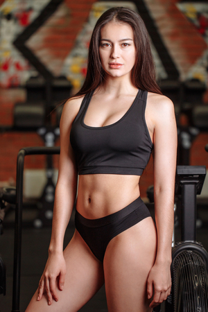 Girl wearing black top and pants posing in gym Stock Photo