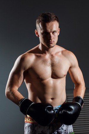 handsome man or healthy boxer or Thai boxer with six pack wearing boxing gloves
