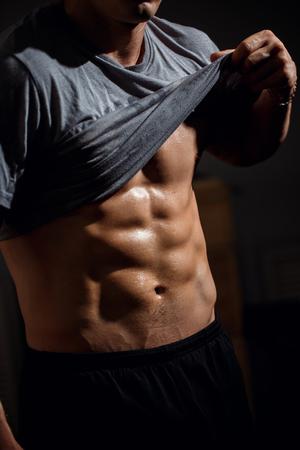 Torso de modelo de fitness atlético fuerte mostrando seis abdominales