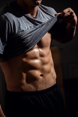 Hombre con torso musculoso mostrando six pack abs