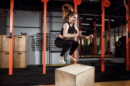 Fitness woman jumping on box training at the gym, cross fit exercise Stock Photo