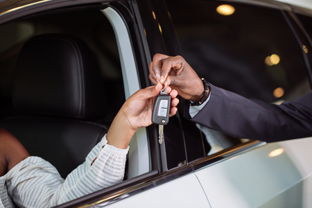 Sales situation in car dealership, young african couple gets the key for new car Stockfoto
