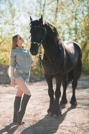beautiful brunette girl with long hair posing with a red horse in forest Reklamní fotografie