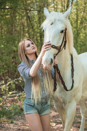beautiful girl stroking horse outside 스톡 콘텐츠