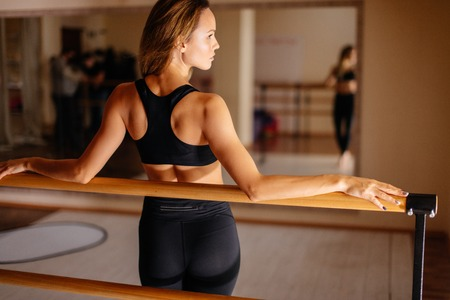 woman dancer posing near barre in ballet studio.