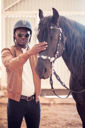 african Man wearing sunglasses near black horse in hangar