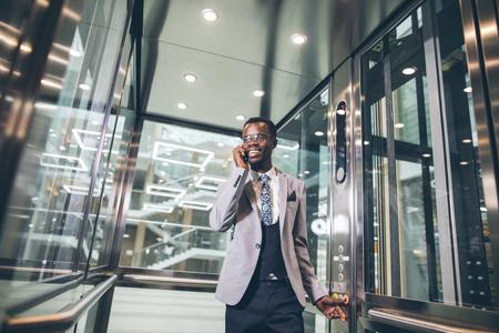 afroamerican businessman in modern glass elevator talking on phone Stock Photo