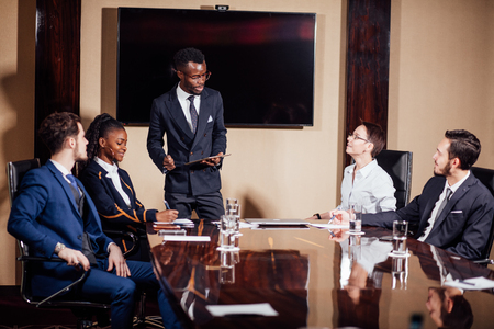 African American business man giving presentation to associates Stock Photo