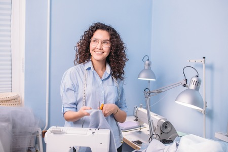 happy tailor is standing with scissors and fabric in room Stock Photo