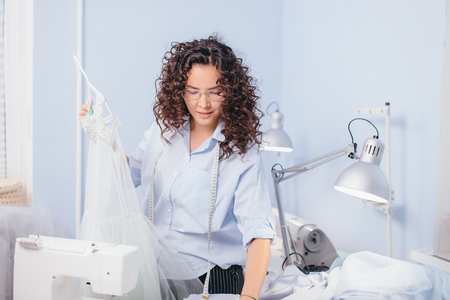 dressmaker designing nightgown at workplace Stock Photo