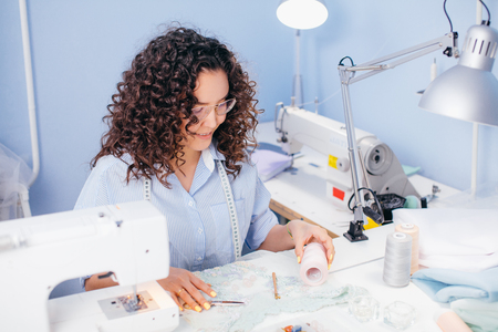 dressmaker in glasses matching thread to fabric at studio