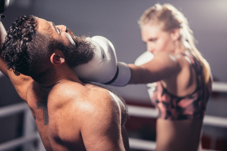 Man get hit by woman Boxer in ring Stock Photo