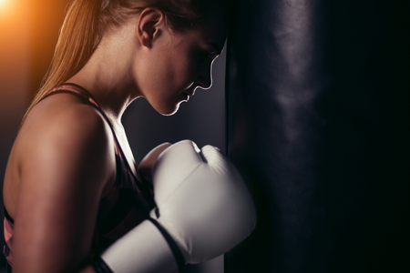 fighter girl in gym with boxing bag. Long hair woman fitness model