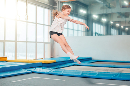 Girl jumping high in striped tights on trampoline.