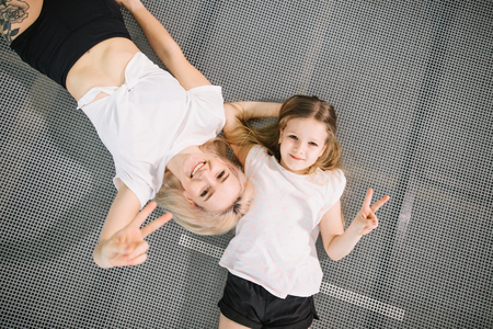mother and little daughter playing at playground and lying on trampoline Banco de Imagens