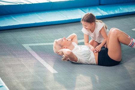 mother and little girl playing at playground and lying on a trampoline Stockfoto