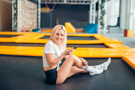 Caucasian women play with her smart phone in trampoline