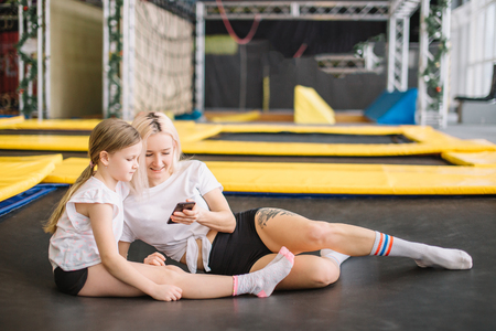 Instuctor and a girl relaxing after workout sitting on mat, using phone in gym Stock Photo