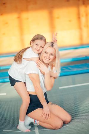 pretty siters girls having fun indoor. Jumping on trampoline in children zone