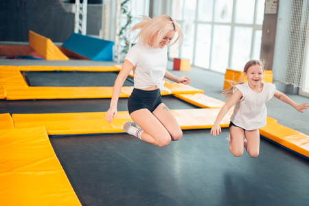 mother and daughter jumping on trampoline and doing split Stockfoto