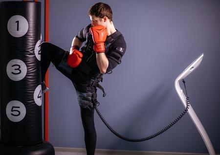 man training knee kick. A kickboxer wearing suit of electric stimulation