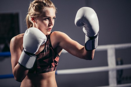 Female Boxer wearing gloves posing in boxing studio