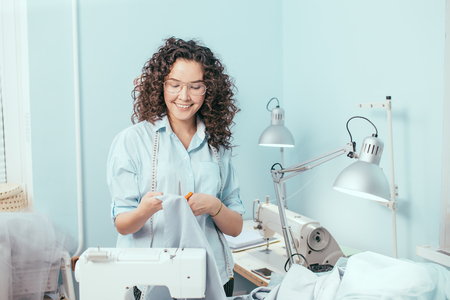 tailor looking at blue fabric in her arms at work Stock Photo