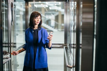 adult businesswomen in suit using smartphone