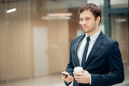 Confident man holding coffee cup and using his smart phone while walking in hall