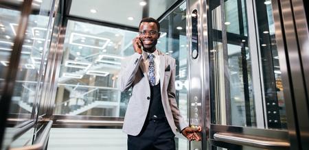 afroamerican businessman in modern glass elevator talking on phone Stock fotó