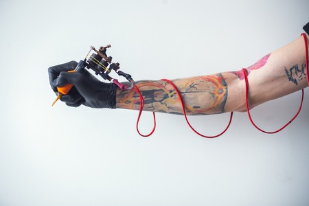 hand tattoo artist with the tattoo machine
