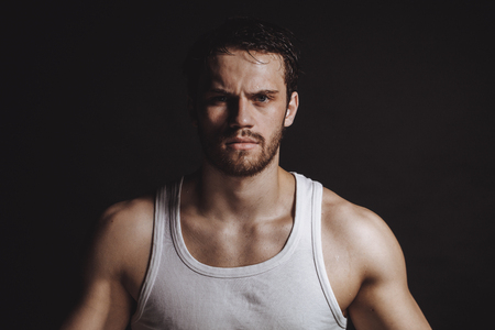 closeup image of strong sweaty sportsman in white shirt after physical trainings