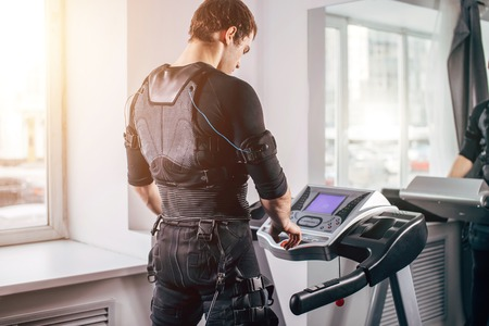 Man in black suit for ems training running on treadmill at gym Stock Photo - 97270280