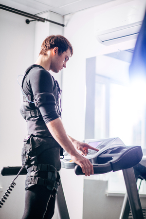 Man in black suit for ems training running on treadmill at gym Stock Photo