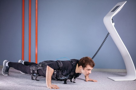 EMS male doing push ups in gym while connected to electric muscle stimulator Stock Photo
