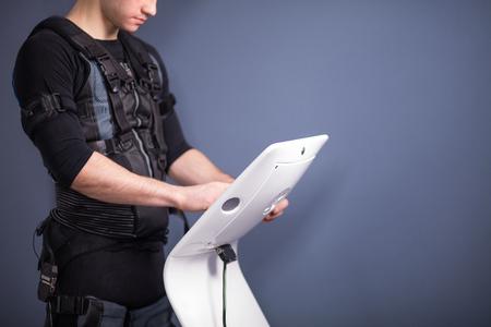 athlete regulating intensity of ems electro muscular stimulation machine Stock fotó
