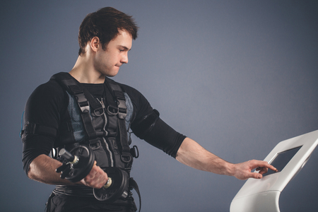 man in Electrical Muscular Stimulation suit standing with dumbbells Imagens