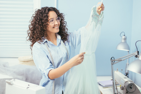 happy seamstress holding hanger with nightgown indoors