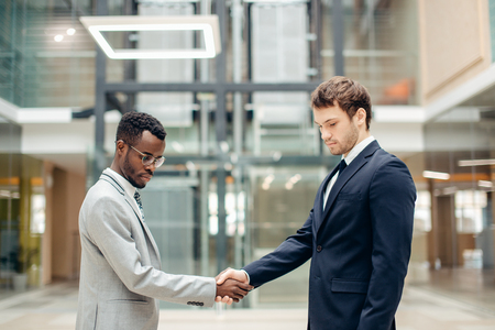 two multiracial businessmen handshaking in modern office for end of great deal