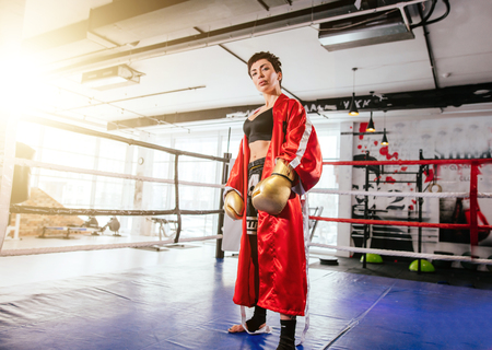formidable woman in sporty equipment for boxing looking at camera on ring at gym Banque d'images