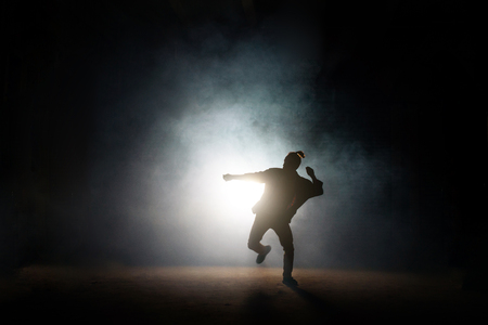 dancing pose of male on one leg on the dark background