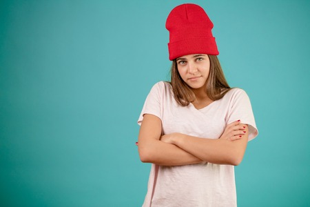 close up shot of model in red cap standing with crossed arms. Stock Photo