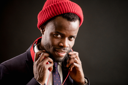 young handsome talented Afro singer in headphones and red cap