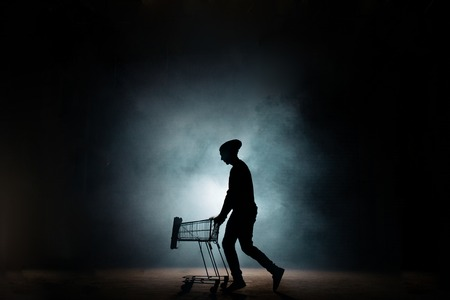 young male in casual clothers drawing an empty cart on the street Stock Photo