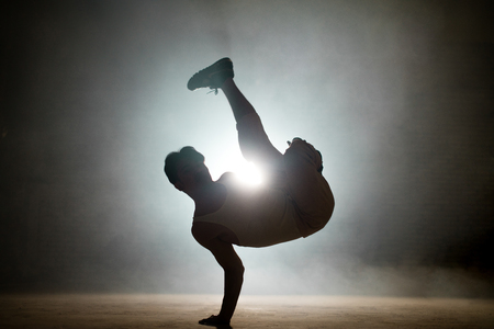 man with dark hair learning basic stunts of breakdance outside Stock Photo