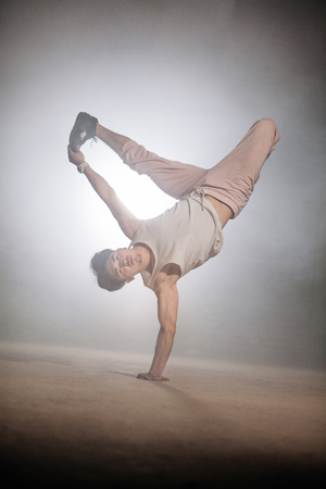 young dancer is showing L-kick. difficult freeze. athletic style. handstand