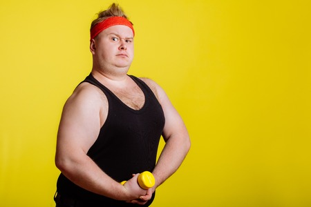fat man with dumbbell on yellow background. Motivation for fat people Banque d'images