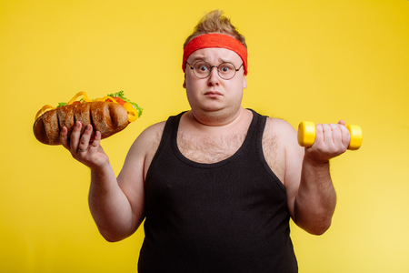 Fat man choise between sport and fastfood Archivio Fotografico - 99139476