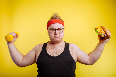 fat hungry man show biceps with hamburger and dumbbell