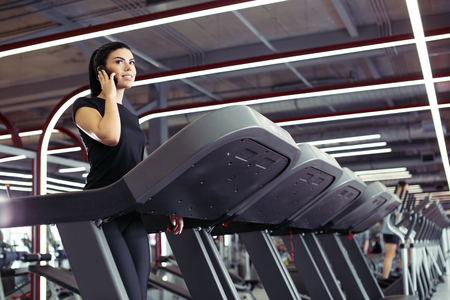woman smiling while talking on mobile phone while running on treadmill Banque d'images